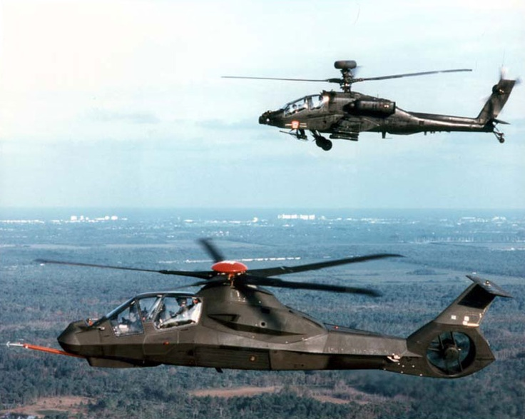 A Boeing Sikorsky RAH-66 Comanche helicopter is joined in flight by a Hughes AH-64 Apache