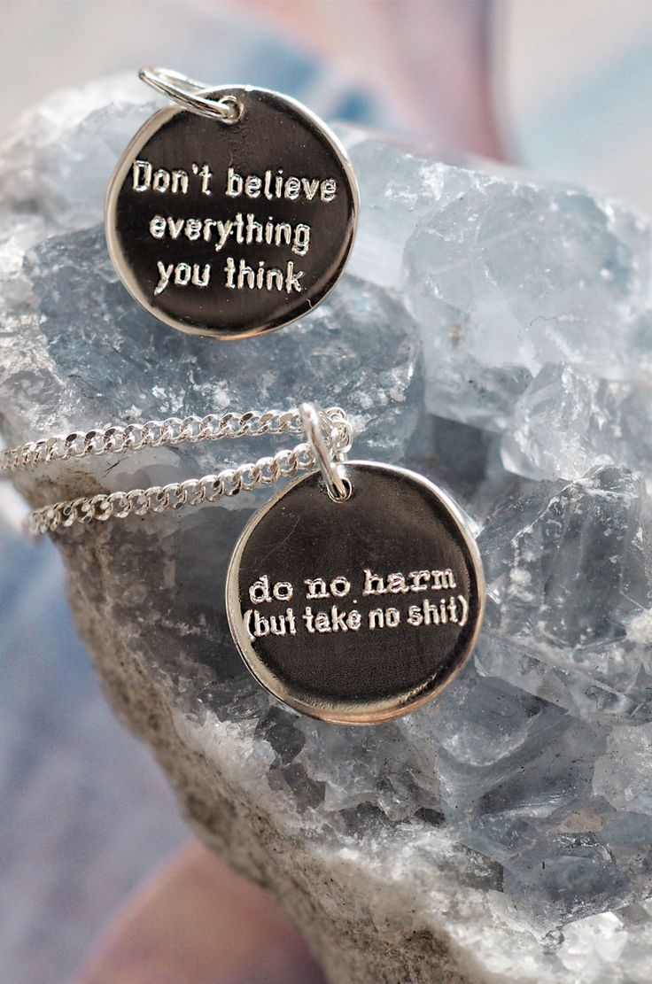 """Tiny minimalist sterling silver round pendants with simple font motivational saying """"Don't believe everything you think"""" and """"Do no harm but take no shit"""""""