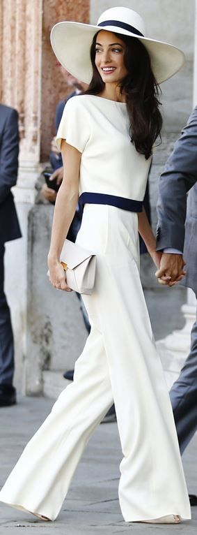 Amal Alamuddin in white pants, short sleeve top, and clutch handbag that she wore in Venice