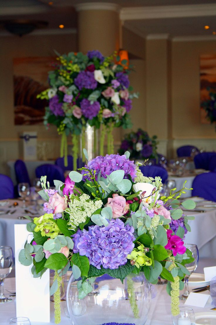 Tall and short luxury wedding flowers... Plump moundy arrangements... hydrangeas, rose, tropical orchids and trailing green amaranthus sat on either gold fish bowls or tall cylinder vases. Tall and short arrangements draw the eye around the room creating wow factor impact.