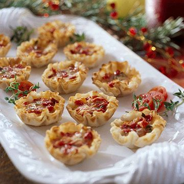 Tomato Quiche Tartlets - Elegant and festive, these bite-size tarts are filled with dried tomatoes, basil, and cheese!    More appetizer recipes: http://www.bhg.com/christmas/recipes/holiday-buffet/