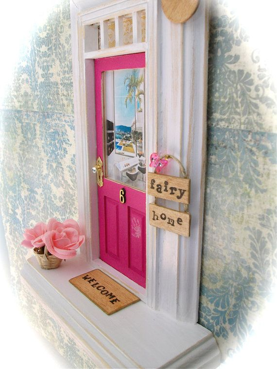 Pink fairy door with a view inside and a ledge to leave tiny presents.