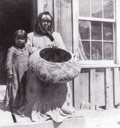 Pomo woman with child holding large basket embellished with trade beads. Native American Indian Basketry - Gene Quintana Fine Art - Indian