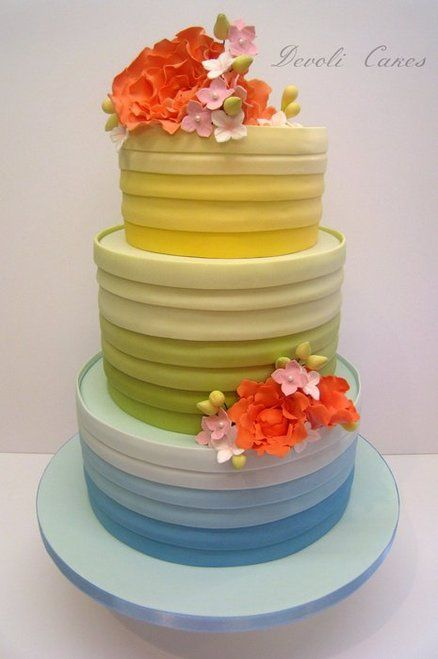 Blue, yellow and green ombre wedding cake with orange and pink flowers