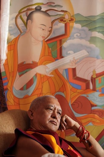 Lama Zopa Rinpoche resting under a painting of Nargajuna