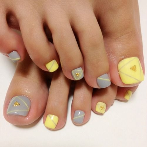 Cute pastel pedicure in soft shades of yellow and gray. Read more on www.producingfashion.com
