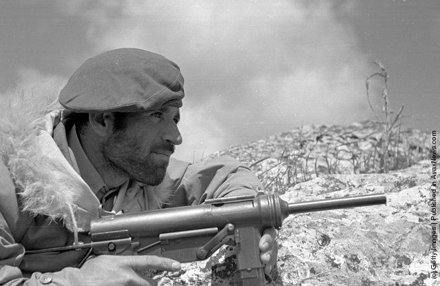 A Greek commando soldier, wearing a fur-collared jacket supplied by the Americans, waits for a guerrilla target to emerge during the Greek Civil War. (Photo by Bert Hardy/Picture Post/Getty Images). 22nd May 1948