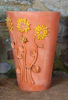 Il Vaso decorativo con fiori di Girasole appartiene alla nuova collezione della gamma terrecotte artstiche. E' un vaso lineare liscio in terracotta, decorato con girasoli in rilievo completamente fatti a mano. Questo vaso, come tutta la collezione, non assolve solo la sua funzione di recipiente per fiori o piante, ma è un esclusivo oggetto di arredo per interni e da giardino. I girasoli possono essere trattati con vernici colorate oppure lasciati del colore naturale della terracotta…