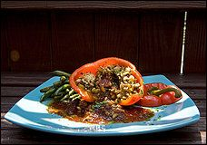 Stuffed Peppers with Ancho Sauce - Mint and cinnamon flavors enliven these peppers, a favorite in Persian cooking. The addition of the ancho sauce lends a bit of spice and body. #veg
