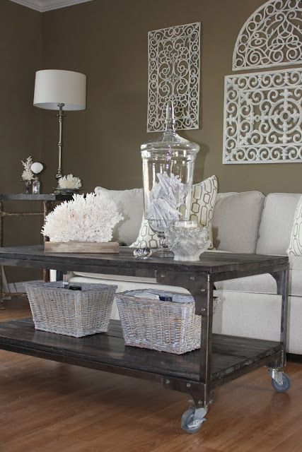 SPRAY-PAINTED RUBBER DOOR MAT AS WALL ART. and love the wheeling coffee table with wicker baskets for an extra touch!