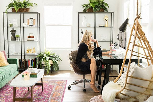 A blogger's bohemian inspired home office with a wooden hanging chair and a green velvet sofa