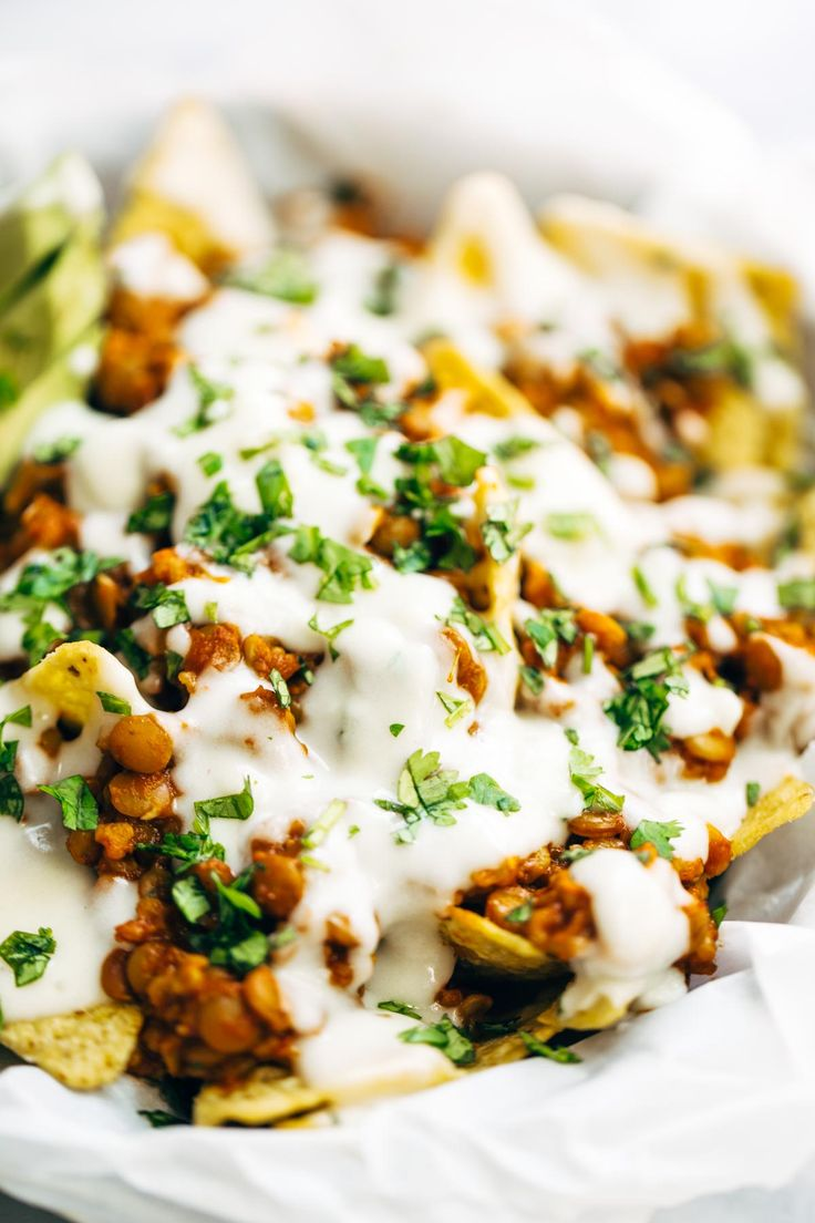 Spicy Lentil Nachos with Three Cheese Sauce - you will not believe how good these are! Saucy lentil filling and velvety homemade cheese sauce, topped with all your favorite things. Vegetarian. | pinchofyum.com