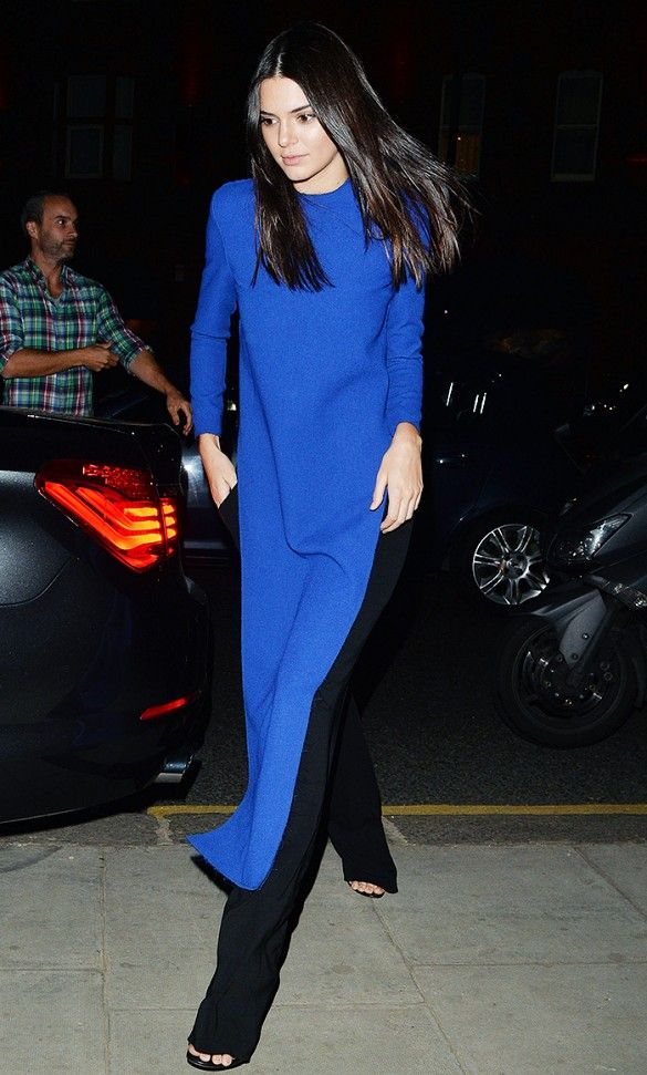 Kendall Jenner wears a royal blue statement top, black trousers, and simple sandals