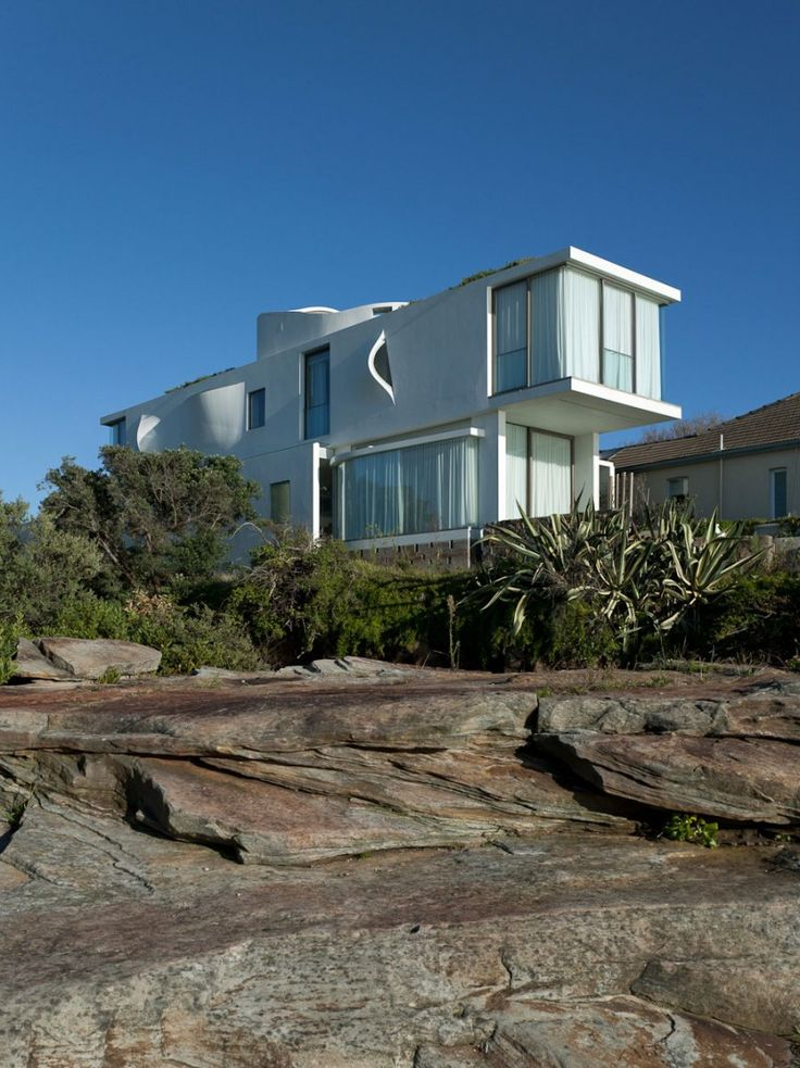 Perched on a slope overlooking the ocean in Sydney, Australia, this modern residence by Chris Elliott Architects is a marriage of bold and demure.  The basement grotto is brightly colored while the rest of the house maintains a more subdued palate.  Seacliff House was designed to house a family of four and was completed in 2007.