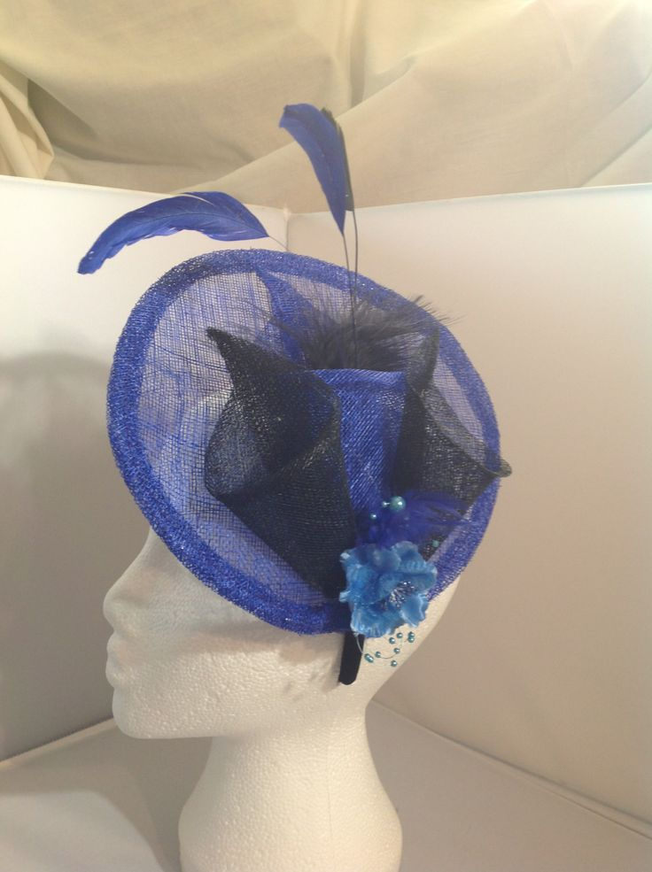 The Danielle is a large fascinator on a black head band the base is large sapphire sinamay with a centre piece of three orchid flowers one sapphire blue two onyx black with matching feathers and sapphire blue flower and pearl detailing to finish. $90 AUD.