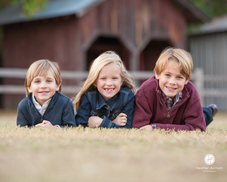 Portrait of kids/siblings laying in the grass in front of a barn. Birmingham AL kids and family lifestyle photographer. Fall family portrait session.  http://www.heatherdurhamphotography.com