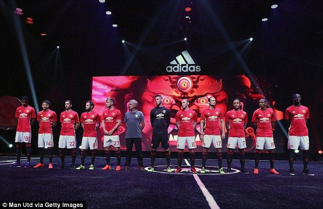 Jose Mourinho and a selection of his players pose in United's new home strip during an official launch