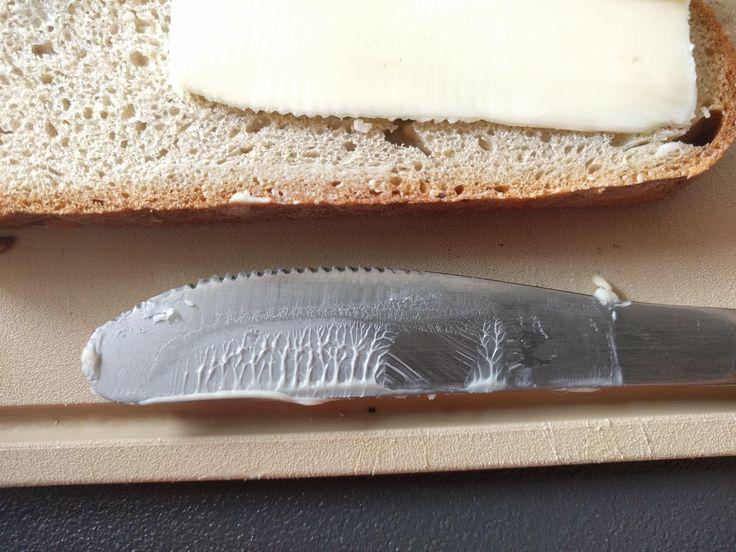 The butter stain on the knife resembles a forest and a