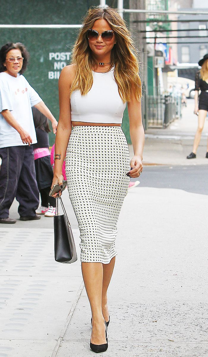 Chrissy Teigen in a polka dot skirt, white crop top, and black heels: