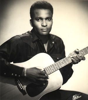 Country singer Charley Pride was born on March 18, 1938, into a sharecropping family with 11 children. Drawn to the radio music of Hank Williams Roy Acuff, he acquired a Sears Roebuck guitar and taught himself to play at age 14. Pride hoped to make his name as a baseball player, and played in the Negro Leagues for some time, entertaining teammates on the bus with his guitar and singing, and gaining stage experience by joining bands in performance from time to time.