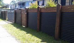 metal Privacy Fence   Wood and corrugated metal create a visually interesting divider...