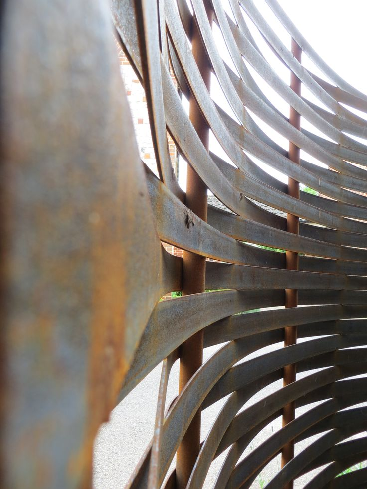 curved woven steel fence by www.steelscapes.co.uk. Once rusted the brown tones take on an organic appearance despite being made from mild steel. Here their fence is being used to screen an oil tank.