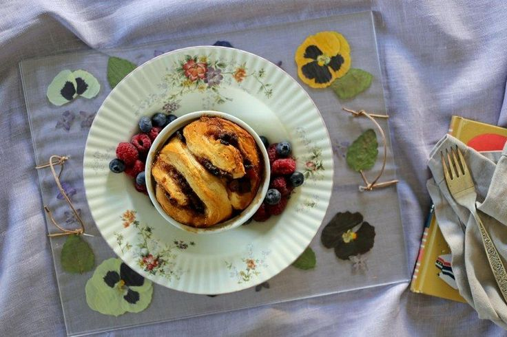petit déjeuner romantique - dessert au chocolat garni de baies et des fleurs de pensées comestibles éparpillées autour de l'assiette
