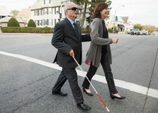 Woman assisting man with cane to cross the street.