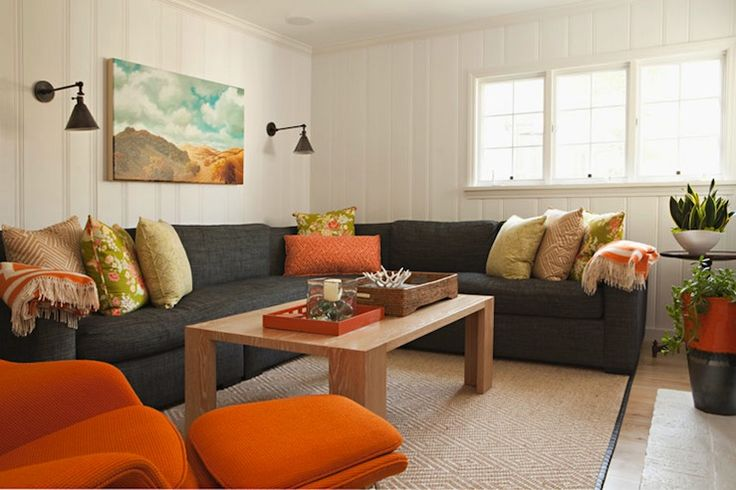 Fun orange & gray family room design with charcoal gray linen sectional sofa, modern rectangular coffee table, black leather bound diamond jute rug, orange recliner chair paneled walls.