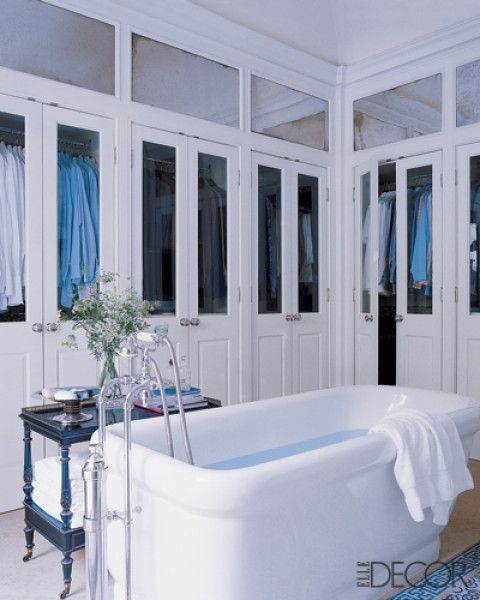 The spacious master bathroom of the Bel Air, California, home interior designer Michael S. Smith shares with James Costos does double duty as a dressing area with glass-front closets; the Town tub and fittings are by Smith for Kallista.
