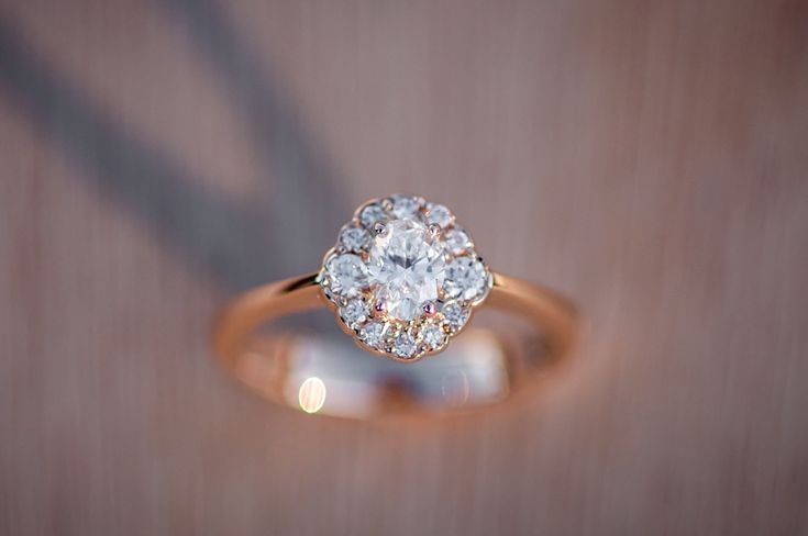 Oval cluster diamond and rose gold engagement ring.