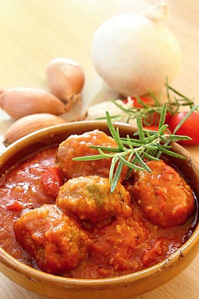 Opečené šišky z mletého hovězího a vepřového masa servírované polité omáčkou z leča, hrášku a dalších ingrediencí.