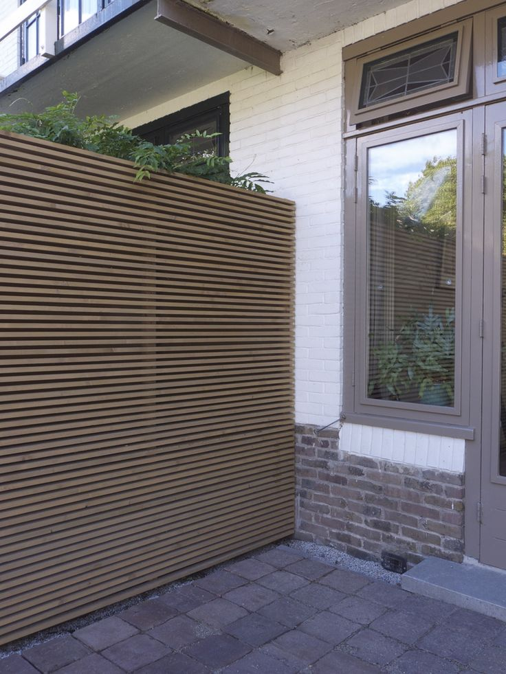 Thin-Slat Fence with Planter on Top: Think 'white wall' has height limits but this extends to obscure next door