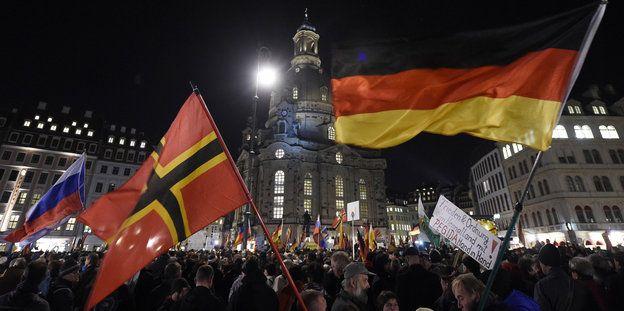 Sagt das ab!  Wo Pegida marschiert und der Galgen für Merkel und Gabriel reserviert ist. In dieser Stadt soll gefeiert werden? Nein danke.Menschenmenge mit Flaggen im Dunkeln bei Pegida in Dresden