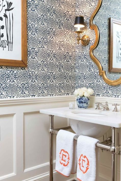 """New wainscoting adds architectural interest to a windowless powder room, made cheery with Galbraith and Paul's Pomegranate wallpaper. """"I love bold wallpaper in small spaces,"""" Casey says. Sconce, Visual Comfort. Console and Sink by Urban Archaeology; faucet by Waterworks. Towels, Leontine Linens."""