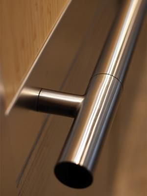 Sextant Handrail with Cylinder finials in Satin Stainless Steel, shown in CabForms 2000-N Elevator Interior with upper inset panels in Bamboo wood veneer; lower inset panels in Stainless Steel with Seastone finish and Cinch pattern; stiles and rails in Stainless Steel with Seastone finish