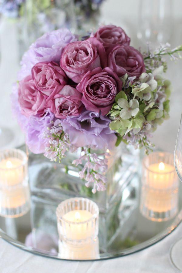 赤紫の丸いバラとパープルのトルコキキョウを使った会場装花。スクエアなガラス花器を使用し、モダンでスタイリッシュな印象のゲストテーブルに。 下にはミラープレートを敷くことで、花や光が映り込んでより華やかになります。