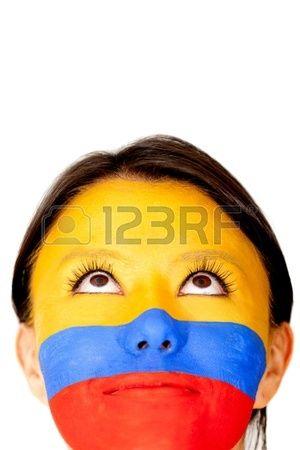 Mujer mirando hacia arriba, con la bandera de Colombia pintada en su rostro.. Foto de archivo.