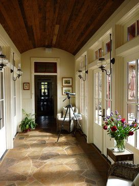 Enclosed breezeway connecting shop and house - windows and French doors on east side, solid wall w/bookshelves on west side.