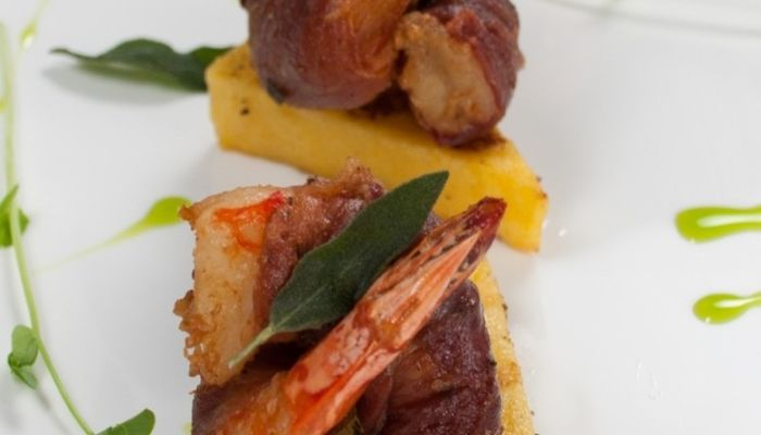 A wedge of grilled polenta sits under a seafood dish