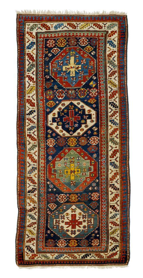GENDJE antique.  Blue central field with four medallions, the entire carpet is geometrically patterned, white border with stylised tendrils, strong signs of wear, restored in some areas.  115x280 cm.