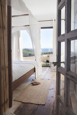 Weathered wood and crisp white linens - perfect bedroom.  Worn leather chairs or overstuffed white canvas chairs by the door.