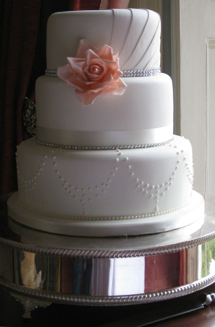 The top tier of this cake was inspired by the pleats in the brides dress. The bottom tier took on aspects of her necklace to make this a truly personal design.