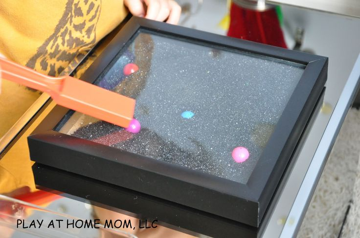 Another excellent idea for magnetic play. A shadow box or deep picture frame can be filled with rice, sand, glitter, or other small particles, as well as interesting magnetic items. Hot glue on a backing piece of wood or cardboard if necessary, and children can use a magnet to hunt around for the hidden items.