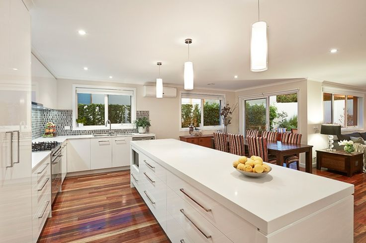 Design is located Highett in Melbourne Australia. The kitchen features modern kitchen designs with spotted gum floor and splashback. White pendant lights and open plan living.