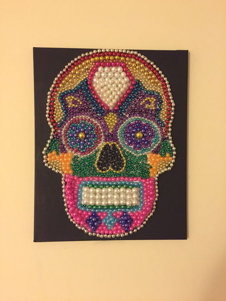 Sugar skull made from Mardi Gras beads. Hot glue on a painted canvas
