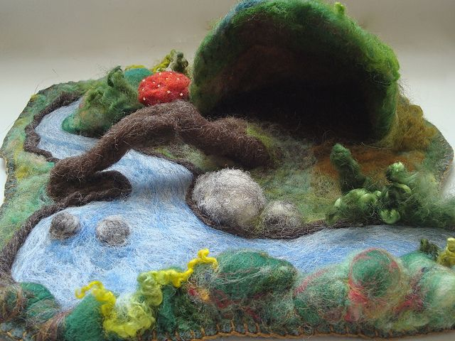 "playscape of felt, featuring a cave and a bridge over felted ""water"""