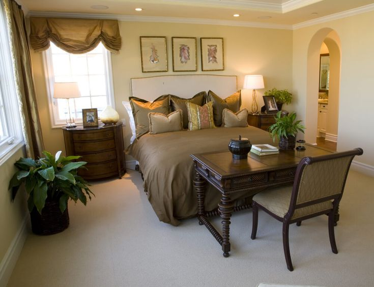 Luxury master bedrooms in mansions - dark brown bed sheets with dark color drapes. Dark wooden chair with dark wooden desk table and night stand. In contrast with beige floor carpet and beige walls. Direct access to master bathroom with no door.
