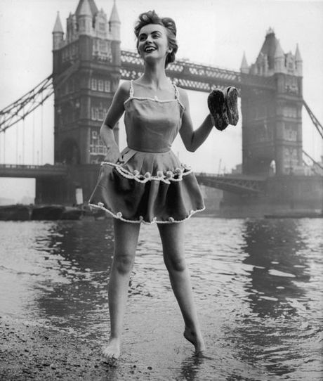 1954: A model wearing an Italian double-purpose sun dress - the loops on the skirt can be buttoned up for paddling - on the banks of the River Thames.  At that time there was a 'beach' there - http://patrickbaty.co.uk/?p=687