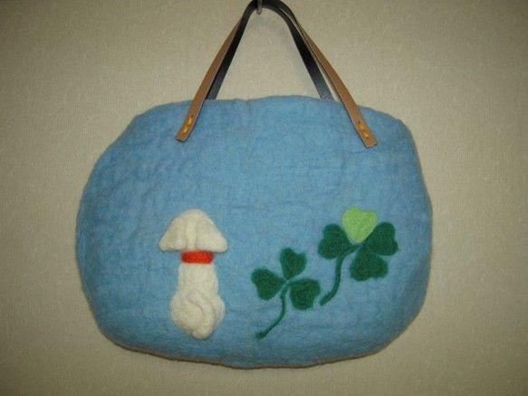 サイズ/縦約22cm×横最大約30cm ころっとした形のバッグです。羊毛フェルトをぎゅっと圧縮して作りました。持っていると温かな気持ちになれると同時に、さわり心地もふわふわしたウールの毛布の様です。表は青空のようなライトブルーの羊毛を使い、白い犬とクローバーを羊毛で刺繍してあります。裏はオレンジ色のの羊毛を使っています。持ち手はベージュのエンビ製です。ちょっとしたお出かけや、コーディネートのアクセントとしてご活用ください。後れ毛が気になったらはさみでカットしてお手入れしてください。お洗濯はウール用洗剤で手洗いし、中温のアイロンで形を整えてください。